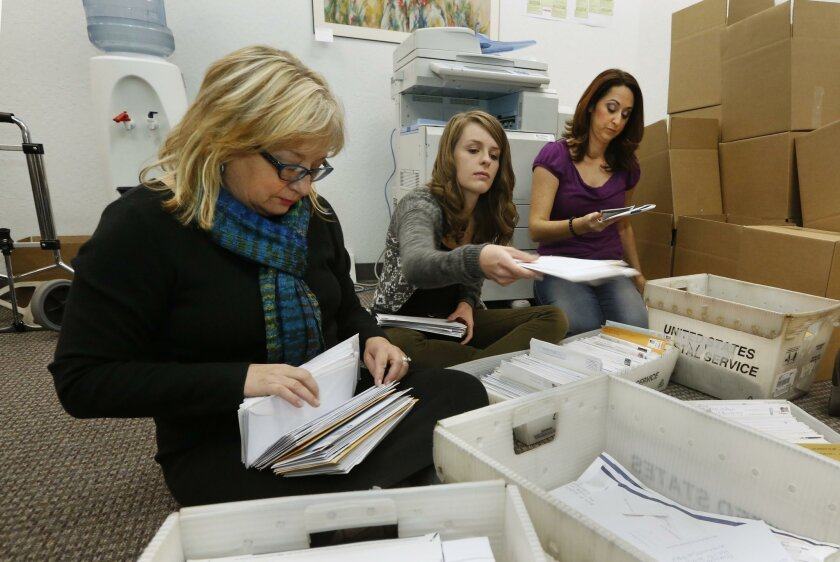 In this photo taken Thursday, Nov. 7, 2013, Karen England, executive director of the California Resource Institute, left, and volunteers Grace LeFever, center, and Christina Hill, sort through stacks of mail with petitions for a referendum to overturn a new California law that allows transgender st
