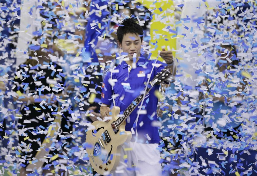 Kei Nishikori of Japan picks confetti off his guitar trophy after beating Taylor Fritz of the United States in the singles championship at the Memphis Open tennis tournament Sunday, Feb. 14, 2016, in Memphis, Tenn. Nishikori won 6-4, 6-4. (AP Photo/Mark Humphrey)