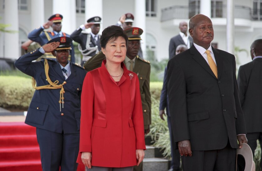 South Korea's president Park Geun-hye, left, and Uganda's President Yoweri Museveni, right, stand for the national anthems at State House in Entebbe, Uganda, Sunday, May 29, 2016. Uganda and South Korea have signed cooperation agreements that officials hope will lead to transfer of technology as Ug