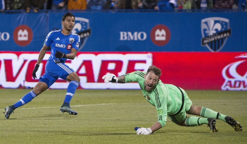 Montreal Impact's Johan Venegas, left, scores against Columbus Crew SC's goalkeeper Steve Clark during the second half of an MLS Eastern Conference semi-final first-leg soccer match in Montreal, Sunday, Nov. 1, 2015. (Graham Hughes/The Canadian Press via AP) MANDATORY CREDIT