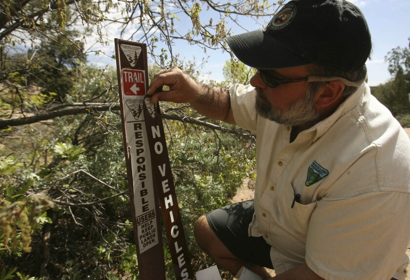 """In this 2010 photo, Bureau of Land Management staffer Tom Heinlein puts a """"No vehicles"""" placard at the trail head of Recapture Canyon near Blanding, Utah."""