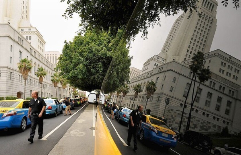 Taxi operators honk their horns while driving around Los Angeles City Hall during a protest. The city sent cease-and-desist letters to three companies that use apps to connect drivers and would-be passengers.