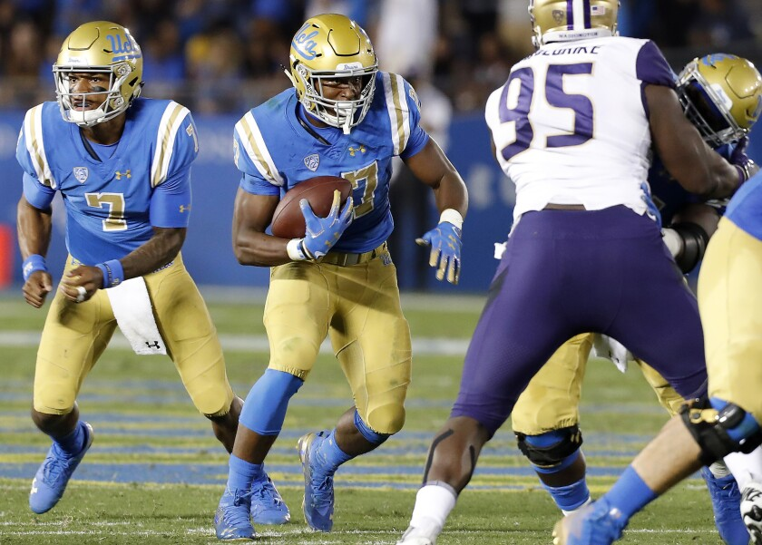 UCLA running back Joshua Kelly (27) looks for room to run against Washington in the third quarter on Saturday at the Rose Bowl.