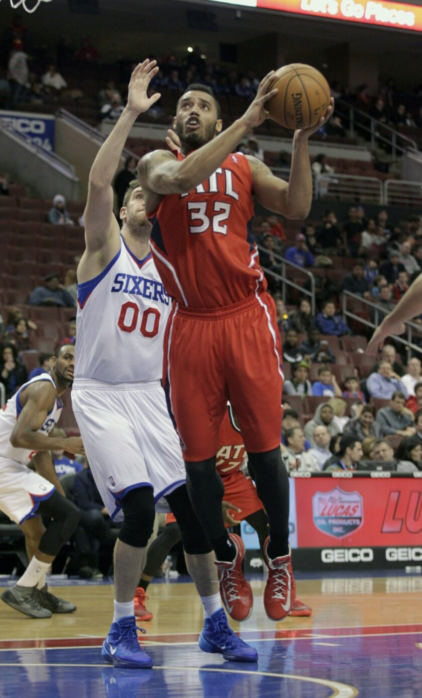 Atlanta Hawks' Mike Scott (32) shoots as Philadelphia 76ers' Spencer Hawes (00) defends in the second half of an NBA basketball game, Friday, Jan. 31, 2014, in Philadelphia. The Hawks won 125-99. (AP Photo/H. Rumph Jr.)
