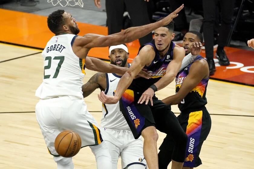 Phoenix Suns guard Devin Booker, right, dishes off around Utah Jazz center Rudy Gobert (27) during the first half of an NBA basketball game, Wednesday, April 7, 2021, in Phoenix. (AP Photo/Matt York)