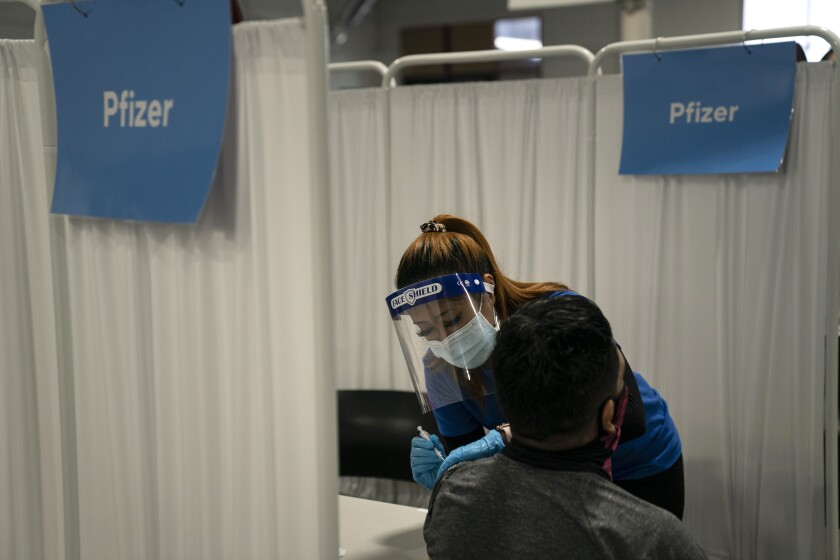 A nurse administers the Pfizer COVID-19 vaccine to a patient in Santa Ana