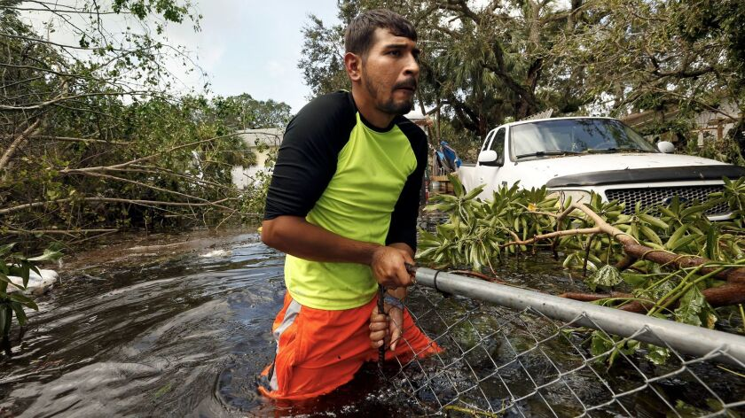 Israel Alvarado, 25, tries to open a gate blocked by fallen tree branches so that he can retrieve a generator in Bonita Springs, Fla.