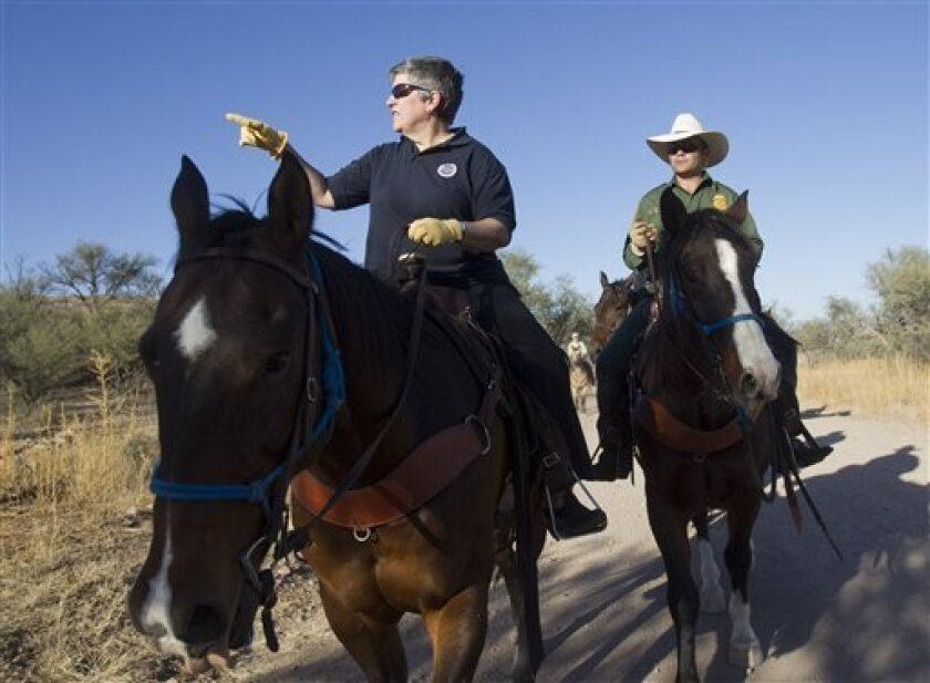 """FILE - In this Oct. 30, 2011, file photo Homeland Security Secretary Janet Napolitano, left, tours the U.S.-Mexico border with Border Patrol agent Steve Venditouli in the Coronado National Forest near Nogales, Ariz. Most illegal border crossers are apprehended along the 2,000-mile long Mexican border in California, Arizona, New Mexico, and Texas. Since the 2006 budget year, the U.S. Customs and Border Patrol has spent more than $1.4 billion on what is described as """"administrative uncontrollable overtime,"""" according to the data provided by the Border Patrol. In practical terms, agents average two hours a day in overtime. (AP Photo/The Arizona Republic, Michael Chow) MARICOPA COUNTY OUT; MAGS OUT; NO SALES"""