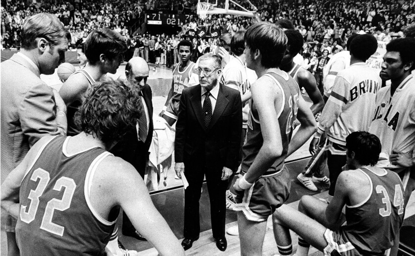 In a black-and-white photo, coach John Wooden wears a suit and talks seriously to players on the court.