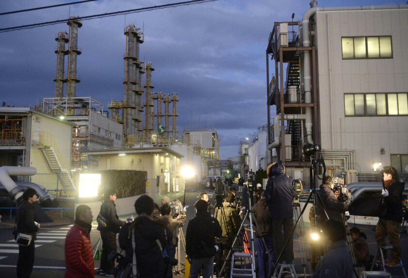 Local media members gather at an entrance to Mitsubishi Materials Corp.'s chemical factory following an explosion in Yokkaichi, central Japan, Thursday, Jan. 9, 2014. The explosion at the factory on Thursday killed scores of workers and injured many others, authorities said. Investigators suspect chemical reaction involving hydrogen caused the blast at the plant. (AP Photo/Kyodo News) JAPAN OUT, MANDATORY CREDIT