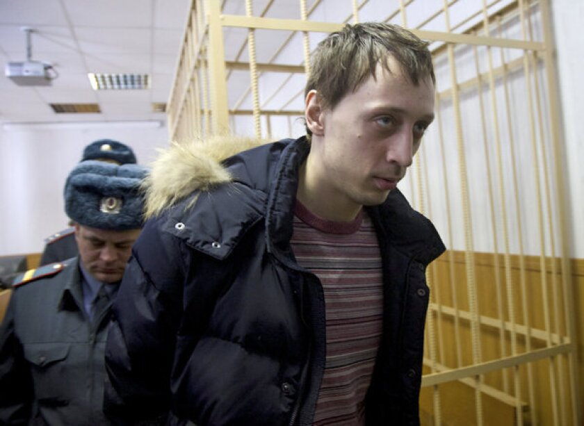 Pavel Dmitrichenko is escorted out of a Moscow courtroom on Thursday. The star dancer is accused of masterminding an acid attack that injured the Bolshoi Ballet's artistic director.