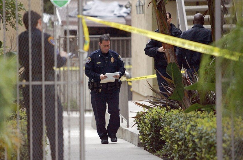 Officers work at the City Heights condominium Friday where two bodies were found.