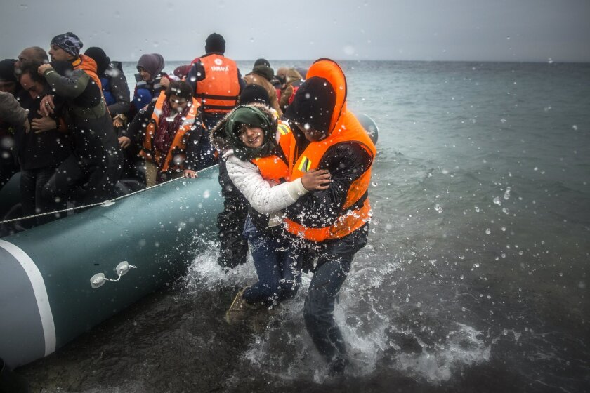 FILE - In this Sunday, Jan. 3, 2016 file photo, refugees and migrants disembark on a beach after crossing a part of the Aegean sea from Turkey to the Greek island of Lesbos. More than a million people reached Europe in 2015 in the continent's largest refugee influx since the end of World War II. Eu