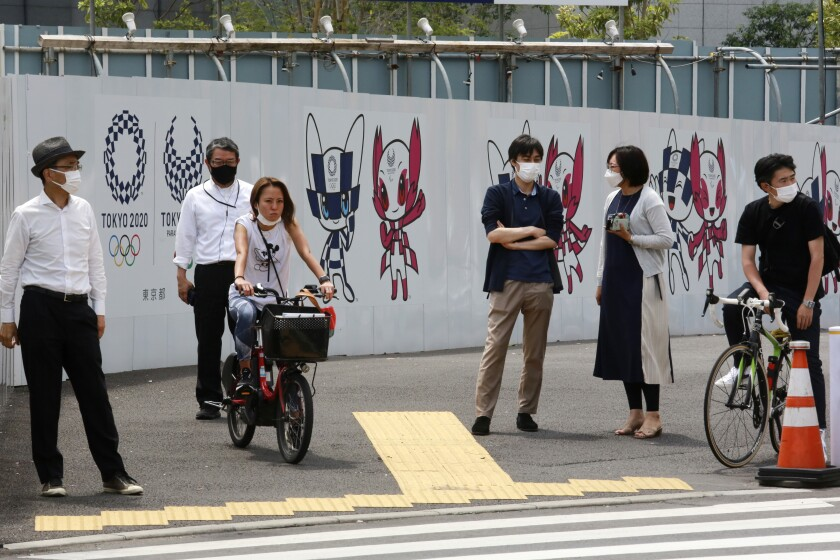 People stand by posters to promote the Tokyo Olympic Games