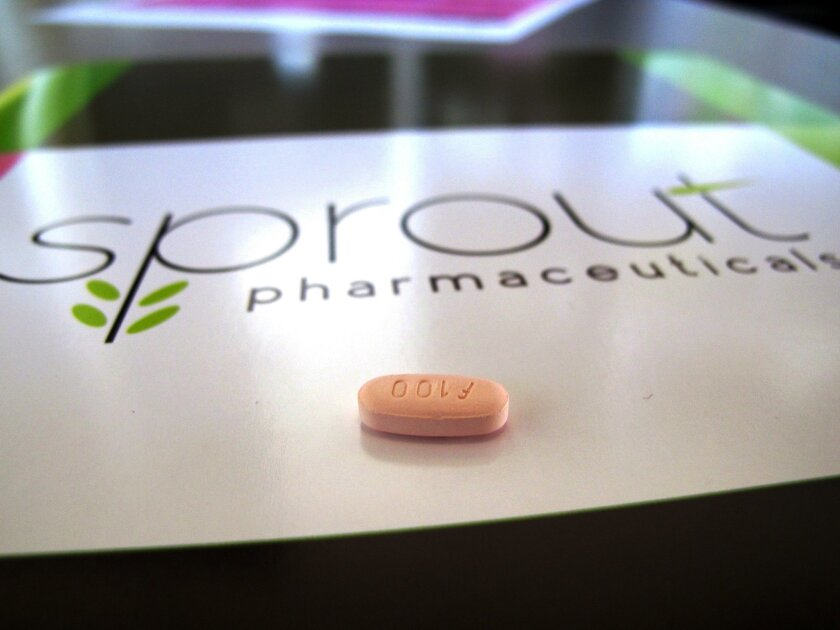 FILE - In this Friday, Sept. 27, 2013, file photo, a tablet of flibanserin sits on a brochure for Sprout Pharmaceuticals in the company's Raleigh, N.C., headquarters. Government health experts on Thursday, June 4, 2015 backed the approval of the experimental drug intended to boost the female sex dr