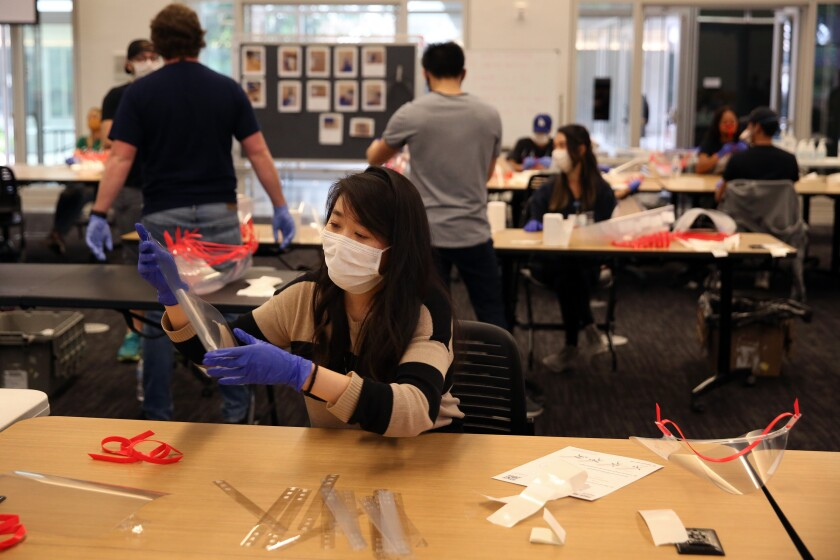 UCLA medical student Vivian Hu makes face shields with other volunteers.