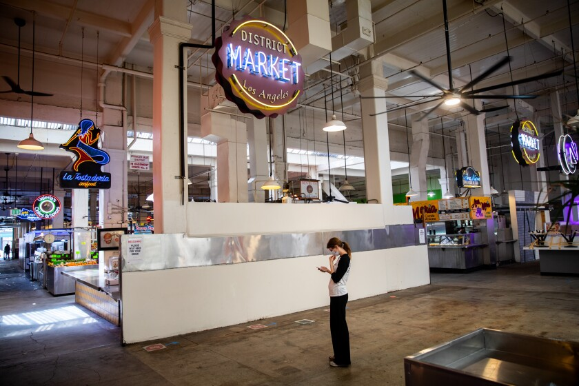 A woman checks her phone in a quiet area of a mostly empty Grand Central Market in downtown Los Angeles