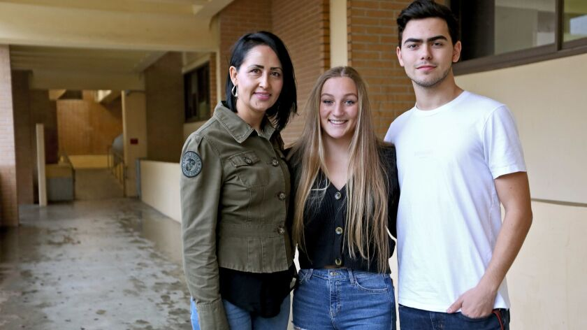 Glendale High School Adopt A Family Club adviser Aurora Alamillo, left, with president Jamie Fritz,