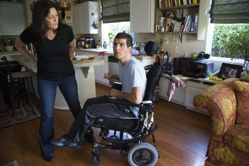Karen Macbeth checks on her son Cheyne Johnston for what he would like for lunch.  Johnston who now lives with his mother suffered a traumatic brain injury last year in a off road motorcycle accident.