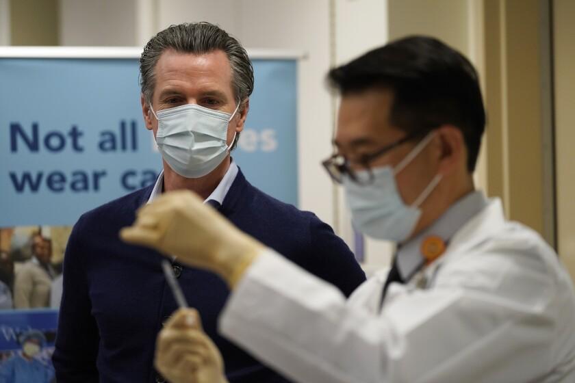 Gov. Gavin Newsom watches as the Pfizer-BioNTech COVID-19 vaccine is prepared.