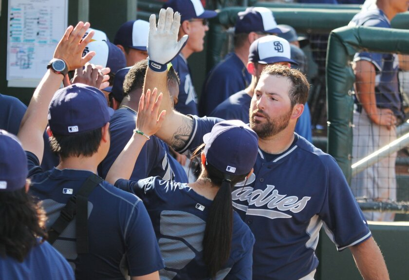 Padres infielder Cody Decker receives high fives in the dugout after hitting a home run in spring training.