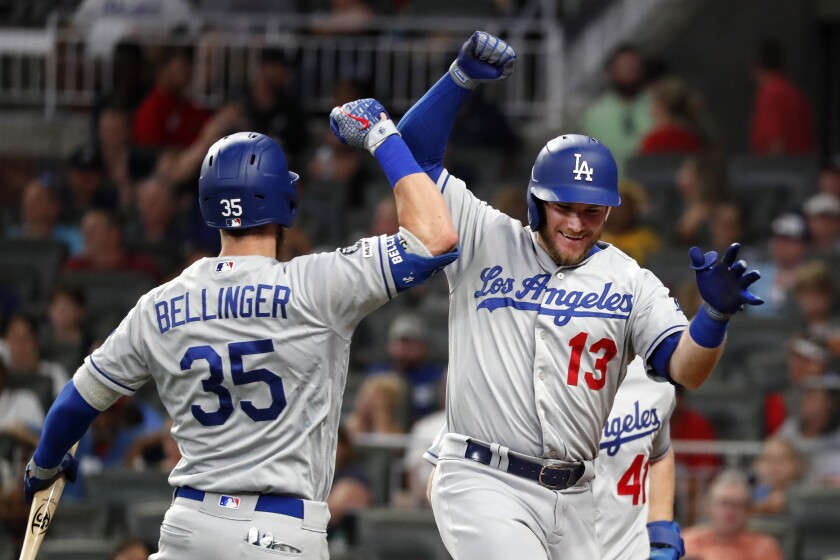 Dodgers' Max Muncy (13) celebrates with Cody Bellinger (35) after hitting a three-run home in the seventh inning against the Atlanta Braves on Friday in Atlanta.