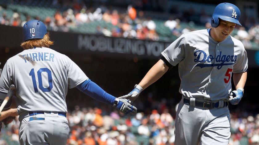 Los Angeles Dodgers' Corey Seager (5) is congratulated by teammate Justin Turner (10) after hitting