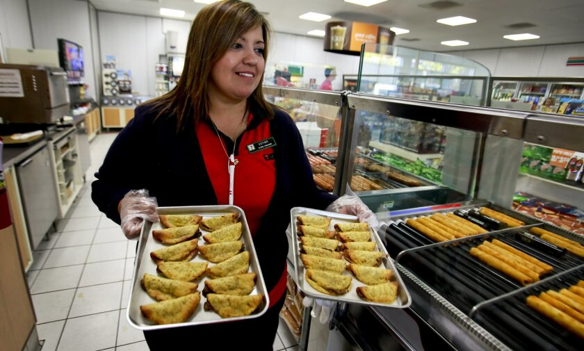 Store manager Esther Armenta takes beef mini tacos from the oven to the display case at the newly remodeled 7-Eleven store on Convoy Street in Kearny Mesa. More than 200 stores in San Diego County received a makeover this summer including new hot-food stations.