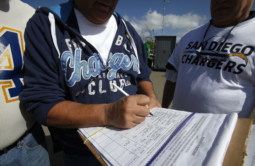 In this April file photo, a Chargers fan signs a petition in support of a downtown stadium ballot initiative.