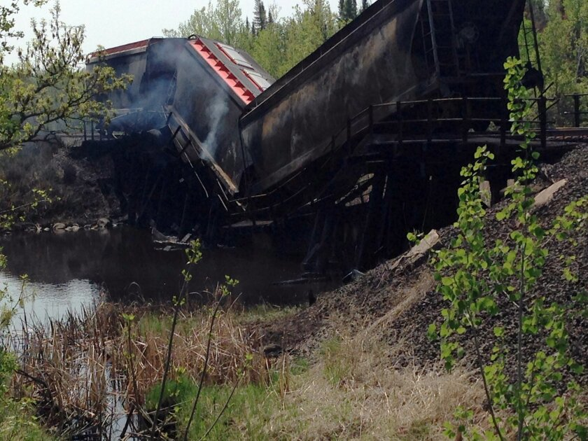 This Wednesday, May 27, 2015 photo provided by the Koochiching County Minn. Sheriff's Office shows train cars on a bridge over the Rainy River in International Falls, Minn. Canadian National Railway officials are working around the clock to rebuild an old wooden railroad bridge that burned and collapsed Wednesday near Minnesota's northern border. The sheriff's office and state fire marshal are investigating the fire's cause. (Koochiching County Sheriff's Office via AP)