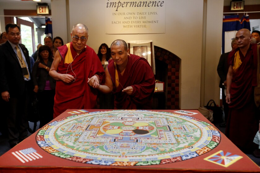 The 14th Dalai Lama, left, with Tibetan monk Sherab Chopel, the principal artist who created the mandala, view it together during a private event in Irvine. The sand mandala was created to commemorate the Dalai Lama's 80th birthday.
