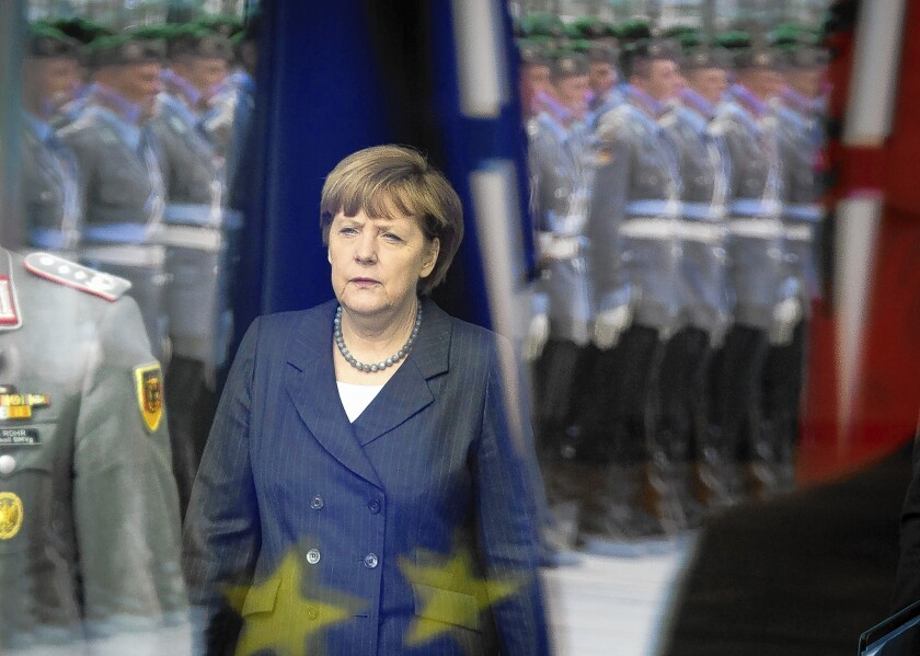 German Chancellor Angela Merkel is seen through a window reflecting an honor guard as she awaits an arrival at the chancellery in Berlin.