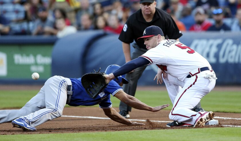 Toronto Blue Jays' Ben Revere dives back to first base as Atlanta Braves first baseman Freddie Freeman (5) handles the throw during the first inning of a baseball game Thursday, Sept. 17, 2015, in Atlanta. Braves pitcher Matt Wisler was called for a balk on the play and Revere was awarded second base. (AP Photo/John Bazemore)