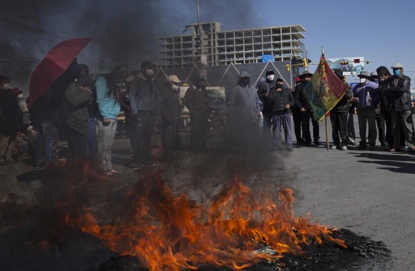 Manifestantes con tapabocas por el nuevo coronavirus queman un neumático durante una protesta contra el aplazamiento de las próximas elecciones presidenciales en El Alto, Bolivia, el lunes 3 de agosto de 2020. La máxima autoridad electoral de Bolivia retrasó las elecciones presidenciales del 6 de septiembre al 18 de octubre. (AP Foto/Juan Karita)