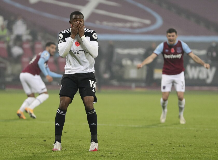 Fulham's Ademola Lookman reacts after missing a penalty and failing to score during the English Premier League soccer match between West Ham United and Fulham at the London stadium in London, Saturday, Nov.7, 2020. (Cath Ivill/Pool via AP)