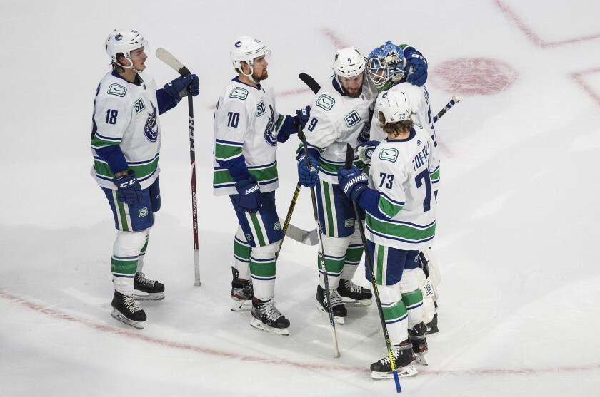 Vancouver Canucks' Jake Virtanen (18), Tanner Pearson (70), J.T. Miller (9), goalie Thatcher Demko (35) and Tyler Toffoli (73) celebrate the team's win over the Vegas Golden Knights in Game 5 of an NHL hockey second-round playoff series, Tuesday, Sept. 1, 2020, in Edmonton, Ontario. (Jason Franson/The Canadian Press via AP)