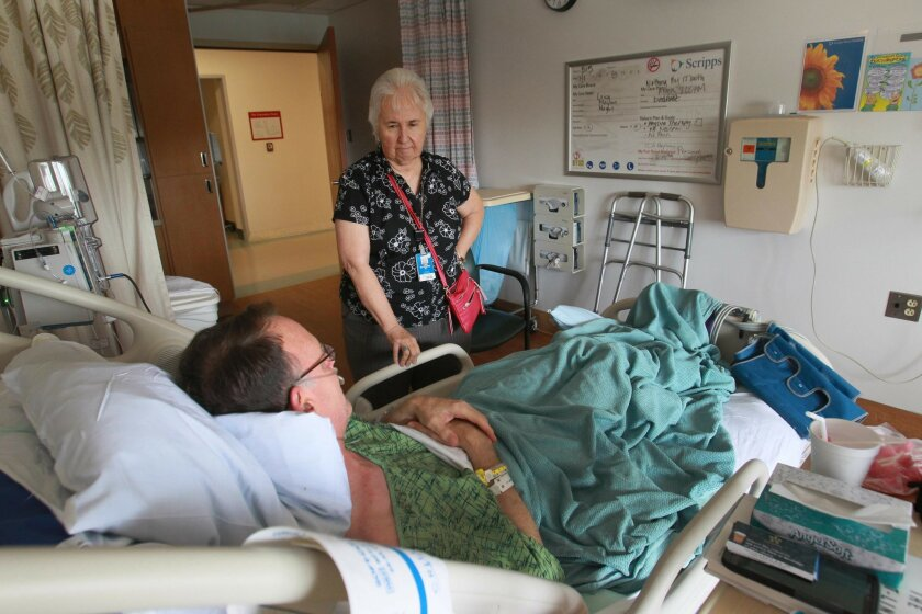 Sister Rosanne McGrath visits patient Michael Harkay at Scripps Mercy Hospital in Hillcrest on July 1. / photo by John Gibbins * U-T