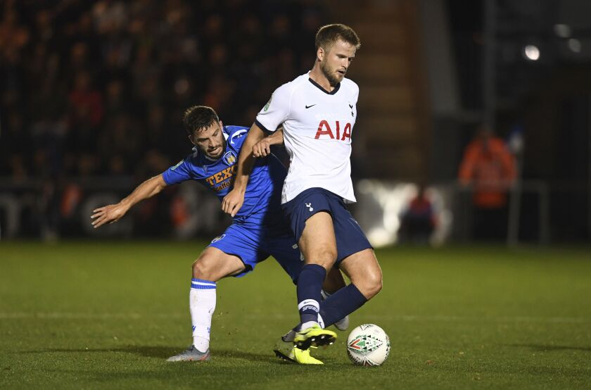 Tottenham Hotspur's Eric Dier, right, shields the ball from Colchester United's Luke Gambin during an English League Cup soccer match between Tottenham Hotspur and Colchester United's at the JobServe Community Stadium, Tuesday, Sept. 24, 2019, in Colchester, England. (Joe Giddens/PA via AP)