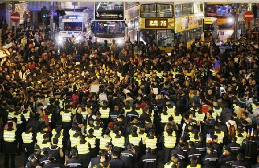 Anti-government protesters, surrounded by police officers, block the main road in downtown, on New Year's Day in Hong Kong Tuesday, Jan. 1, 2013 to call for the resignation of Hong Kong Chief Executive Leung Chun-ying. Several hundred members of a small radical group briefly blocked roads after they were stopped by authorities from marching to Leung's official government residence. At one point, protesters pushed and shoved with police. (AP Photo/Kin Cheung)