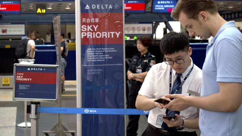 In this July 6, 2018 photo, a staff member assists a passenger near the check-in counters for Delta