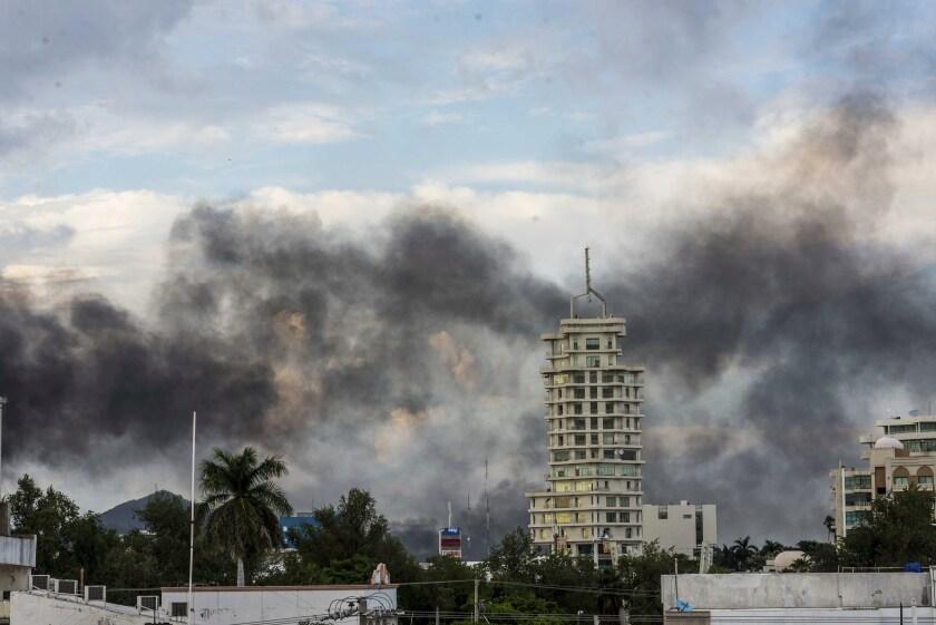 Smoke rises from burning cars amid the gunfight.