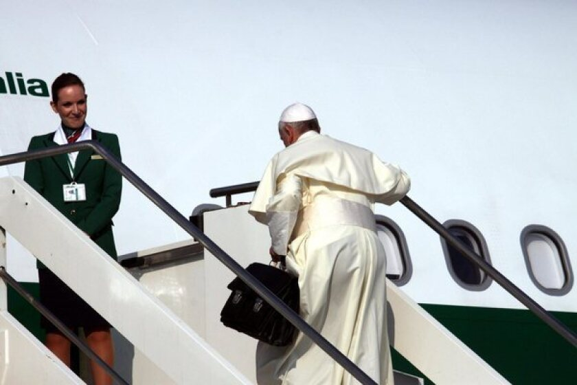 Pope Francis carries his bag up the stairs of his plane Monday as he leaves Rome for Brazil.