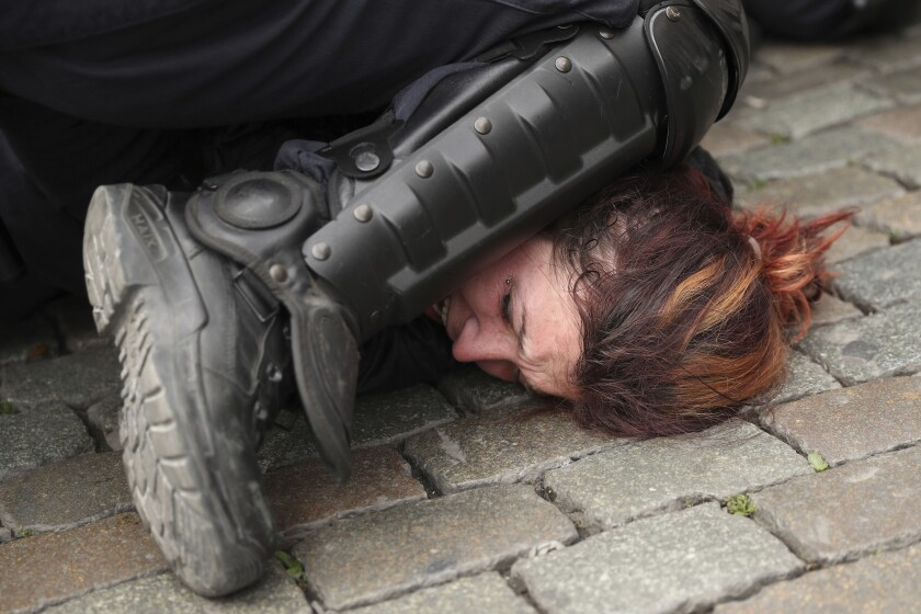 Police pin a woman to the ground during a protest in Brussels in May 2019.