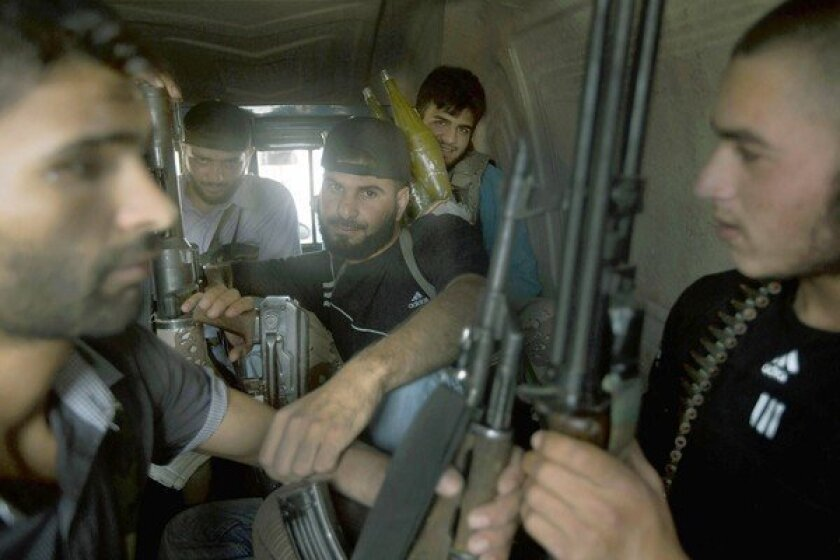Members of the Free Syrian Army rebel group sit in a truck in the city of Qusair, western Syria, en route to battle with Syrian government forces.
