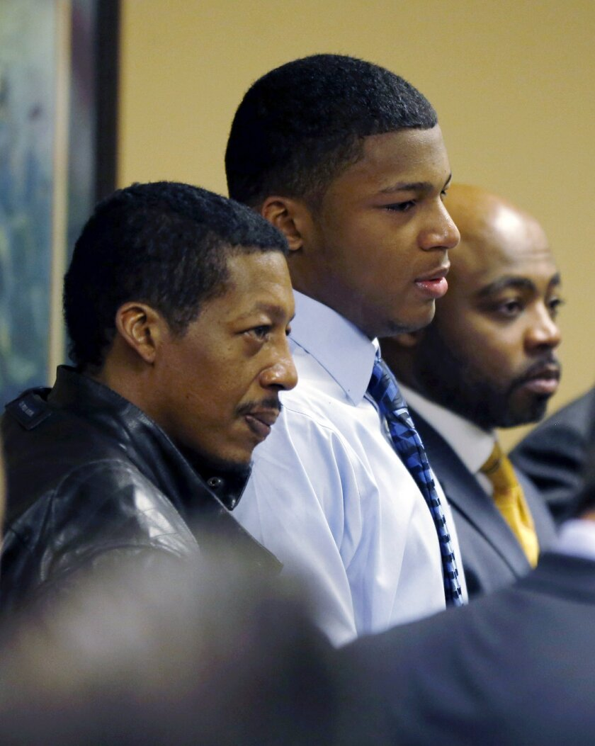 FILE - in a file photo made Sunday, March 17, 2013, Ma'lik Richmond, center, stands with his father, Nathaniel Richmond, left, and attorney Walter Madison after he and co-defendant Trent Mays, 17, were found delinquent on rape and other charges in juvenile court in Steubenville, Ohio. Ma'lik Richmond has been released from a juvenile detention center less than a year after his conviction for raping a 16-year-old girl following an alcohol-fueled party. (AP Photo/Keith Srakocic, Pool, file)