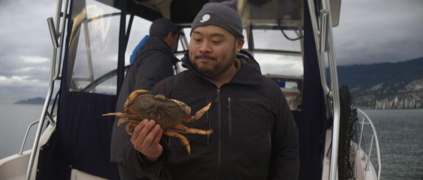 David Chang détient un crabe fraîchement pêché dans la rubrique «Petit déjeuner, déjeuner et dîner» de Netflix