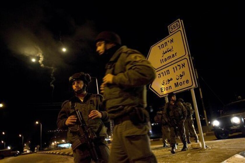 Israeli soldiers man a roadblock at the entrance to the Jewish settlement of Itamar, near the West Bank town of Nablus, early Saturday, March 12, 2011. A Palestinian infiltrated a Jewish West Bank settlement early Saturday and killed five people, the Israeli military said. (AP Photo/Bernat Armangue