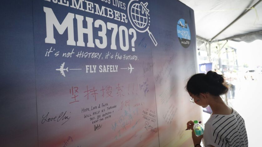 A girl writes a condolence message during the Day of Remembrance for missing MH370 plane event in Kuala Lumpur, Malaysia, on March 3.