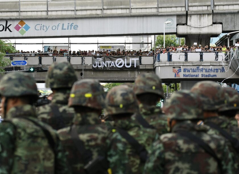 Thai soldiers stand guard as hundreds of pro-democracy activists protest the military coup in the center of Bangkok.