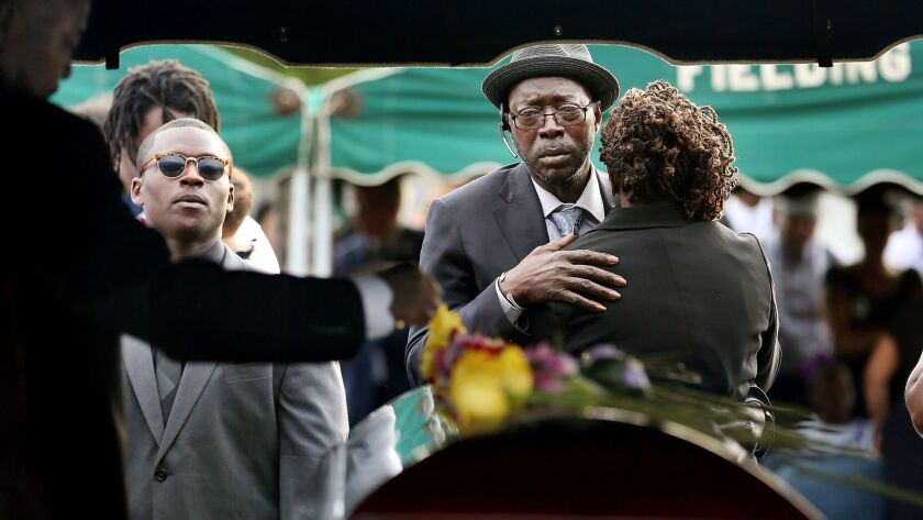 Tyrone and Felicia Sanders comfort each other at the graveside of their son Tywanza Sanders at Emanuel AME Cemetery in Charleston, S.C., in 2015.